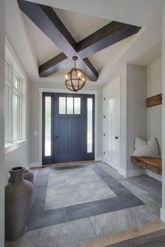 Entry: ceramic tile floor with contrasting color ceramic tile detail, coffer ceiling with box beam cross detail, floating rustic wood bench