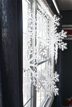 Dollar Store snow flakes, hang from curtain rod in my big living room window.