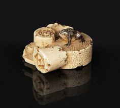 An ivory netsuke 'Toad on a millstone', Japan, around 1900. Carved ivory. Very finely worked depiction of the animal sitting on a millstone-base. Sign. 'Masanao'. L. 4 cm.