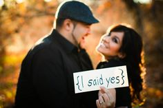 "Nice idea for an engagement photoshoot. A girl said she saw it with the her holding a sign ""He asked"" and he held a rustic sign that read ""She said Yes"""
