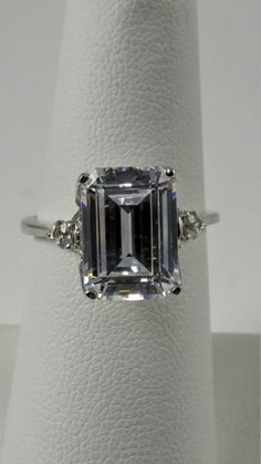 7.50 Carat Total Weight Emerald Cut Solitaire with Round Accents…