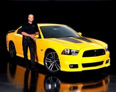 Chrysler racing director Ralph Gilles stands next to a yellow 2012 Dodge Charger SRT8 Super Bee. / Courtesy Chrysler