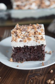 A square piece of chocolate cake topped with a whipped topping and toffee bits.