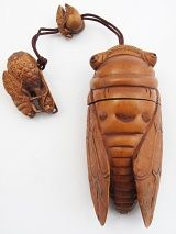 handcarved boxwood cicada inro box has a cicada netsuke bead and sliding cicada ojime bead to fasten the lid closed. In Japanese philosophy, the cicada is a symbol of longevity, innocence, purity, and eternal youth. size: 2 x 4 1/4 inches long.