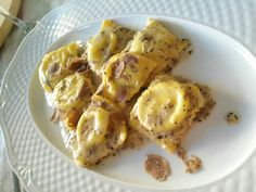 Raviolo con ricotta di bufala su un letto di crema burro e pecorino e scaglie di tartufo bianco