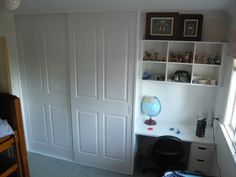 Vinyl wrapped, 4 panel routed, sliding door wardrobe with adjoining desk and overhead shelving