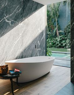 Almond bathtub by Porcelanosa and tub filler from Hansgrohe in silver gray marble-lined bathroom.