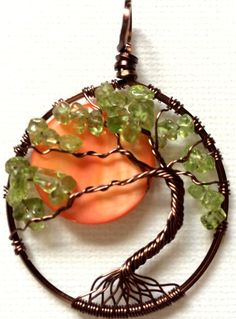 Beautiful handcrafted Tree of Life pendant made with natural peridot gem stone chips on an antique copper tree with an orange mother of pearl