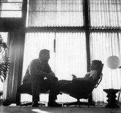 Charles and Ray Eames at home with their Eames lounge.