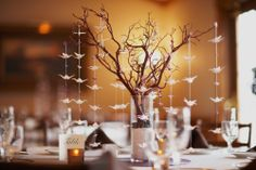 This is such a unique table setting... nature theme of bonsai tree and origami birds. We like it!