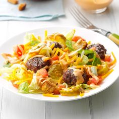 Deluxe Cheeseburger Salad Recipe -I was planning to grill burgers, and then it dawned on me: How about a Big Mac salad? The original recipe doesn't call for a tomato, but it's awesome here. —Pam Jefferies, Cantrall, Illinois