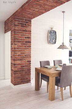 Czerwone cegły ożywiają stonowaną aranżację jadalni w stylu skandynawskim. Prosty drewniany stół i wygodne krzesła...