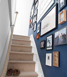 Um corrimão de corda, parede em uma cor marcante e uma galeria de quadros. Um conjunto bonito. Fotografia: William Waldron.