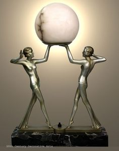 An Art Deco double figure spelter lamp, c. 1930, Germany or Austria, the cold-painted silver metal figures mounted on a beautiful portoro marble base holding aloft an alabaster globe. (hva)
