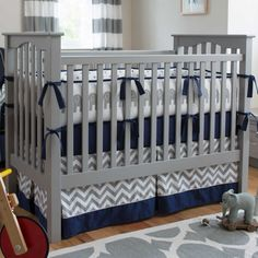 "Crib Bedding Bumper in Navy and Gray Elephants by Carousel Designs.  Our four-sided crib bumpers are produced in one continuous piece and fit standard cribs (using mattresses measuring approximately 28"" x 52"") and meet regulation standards with approximately 12"" long ties and 2-3"" thick batting, so that you can rest easy. Our crib bumper batting is made from recyclable hypoallergenic polyester fiberfill."