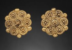"""Earrings Etruscan, 525-500 BC The J. Paul Getty Museum """"Seven rosettes form the decoration of this pair of large Etruscan earrings. Placed in a circular arrangement around a central point, the rosettes were made separately and attached to a backing..."""