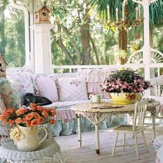Pretty Porch with arch fretwork on the poles. The soft colored pastel floral cushions and sofa makes one want to just sit there and enjoy the flowers