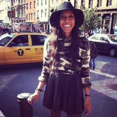 Camo jumper, leather pleated skater skirt matched with a wide brim hat and a cross charm belt