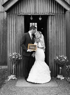 Just married! Bride and groom kiss outside the Mission Church at Avoncroft Museum of Historic Buildings (avoncroft.org.uk). Black and white photograph. Rosie Kelly Photography