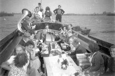 """Skûtsjes werden vroeger ook wel gebruikt voor pleziervaren. Op deze foto een uitstapje van het fanfarekorps """"Apollo"""" uit Grou aan boord van het skûtsje """"De Nijverheid"""" van de familie Mink, ca. 1955."""