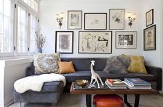 like this look with the arrangement of wall art and the wall sconces.  I have that coffee table.