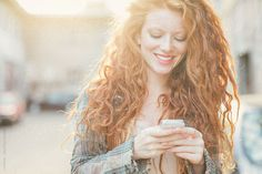 Ginger Woman Texting Outdoors by lumina   Stocksy United