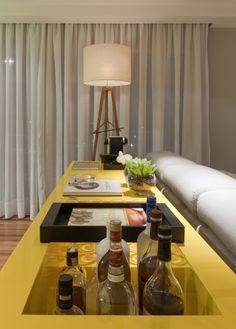 """aparador em laca amarela além de """" vestir"""" as costas do sofá , serve de apoio para o jantar e mesa bar. A cor deixa o espaço mais despojado e informal quebrando os tons neutros"""