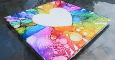 Alcohol Ink Decorated Ceramic Tile using a contact paper resist, canned air, and rubbing alcohol splatter technique.