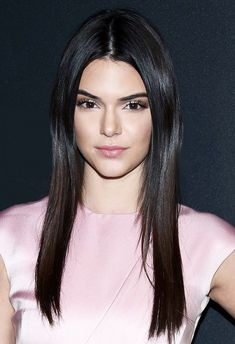 Kendall Jenner's minimalistic beauty look features straight hair, a center part, and extra long lashes