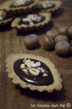 Tartellette alle nocciole ripiene di cioccolato fondente.