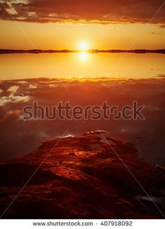 Stock Photo: Sunset with red color in the clouds and the rocks on the shore. Dramatic reflection of the Sun in the still water of a lake in Finland.