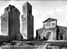 """Una grande basilica romanica e i ruderi di un castello su un colle alla sua sinistra. Poi girando lo sguardo verso destra come in una panoramica, i morbidi monti del viterbese a perdita d'occhio e misteriosi valloni di scura macchia mediterranea alternati a pianori verdi e a campi di oliveti. """"Questa è la terra degli etruschi"""" si disse con una improvvisa emozione."""