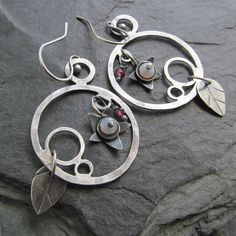 Sterling silver hoop earrings with little flower and leaf charms hanging inside. They are completely hand made by me out of sterling silver and genuine gemstones including pale blue Chalcedony and Garnet. These are light and comfortable to wear, measuring about 1 7/8 long, not including ear wire.