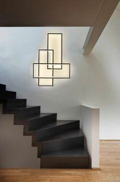 escalier design avec des marches toutes noires, garde corps en pierre noire et grise, ornement artistique sur le mur de l'escalier en forme de trois rectangles qui s'entrecroisent, parquet beige clair et foncé au sol