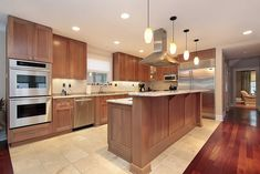 L-shaped wooden kitchen design on tile floor (surrounded by wood floor) with two-tier kitchen island.