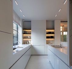 Pennisula kitchen open. Full height cabinets on west wall. Open shelving. All white cabinets. No uppers with lower cabinets