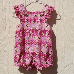 A delightful little romper full of happy bees made of 100% cotton fabrics.  The bees are yellow and black flying about in front of honey comb, of 3 shades of pink.  This romper fastens with bee buttons on the shoulder straps to the front yoke.  The crotch fastens with snaps.  The elastic in the legs  makes for a better fit and creates a subtle ruffle.  All seams are nicely finished.