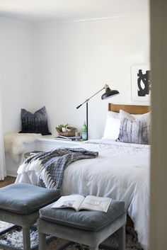 ottomans at the foot of the bed in modern glam bedroom