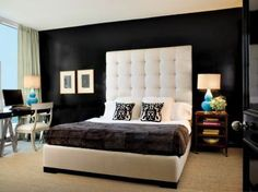 A tufted headboard dominates a dark wall in this masculine master bedroom.
