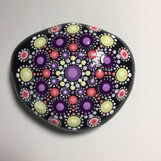 Hand painted with acrylic in Lemon Yellow, Purple, and Coral. Sprayed with a high gloss sealer to protect the colors. Stone size is 3 1/2 X 3.