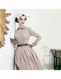 Nan Rees, January 1952 in beige Sirrey Classics dress with grey linen collar and cuffs and John Frederics' Charmer hat, leans against wall with edge of gilt sunburst clock in foreground