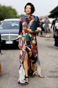 Comme chaque année, les modeuses rivalisent de style, haut perchées sur les pavés de Milan. On s'inspire de leurs looks ! Focus: robe longue avec motifs colorés et asymétriques