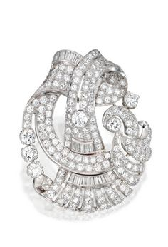 PLATINUM AND DIAMOND BROOCH, CIRCA 1930 Of openwork and scroll design set throughout with round, single-cut and baguette diamonds weighing a total approximately 13.60 carats.