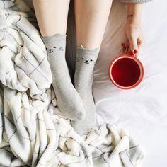 Meia cinza com gatinhos, cobertor quentinho e chá de frutas vermelha na cama.