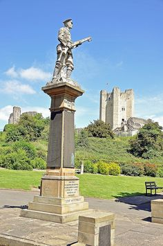 12th century Conisborough Castle, Yorkshire, England with the war memorial to the soldiers of both world wars in the foreground