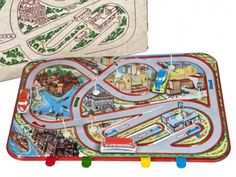Vintage tin litho child's toy from Hungary.   Includes cityscape with three cars and street signs.   Place wind up cars in parking spots and push the lever to make them go around the track.