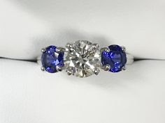 eco-friendly ring with lab-grown carat diamond center and round Chatham-created blue sapphire sides. Call us today for your custom piece: Matching Wedding Bands, Gemstone Engagement Rings, Blue Sapphire Rings, Natural Diamonds, Jewelry Collection, Eco Friendly, Lab, Wedding Ideas, Board