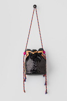 "Bring out your inner fashionista with the Belle Sequin Bucket Bag!  Covered in mini sequins, this bag features a multicolored yarn rope strap & draw string detail.  Finished with a magnetic closure & inside pockets. <br />%0D%0A<br />%0D%0A- 9.5"" length x 9.5"" height<br />%0D%0A- 27"" strap drop<br />%0D%0A- Imported"