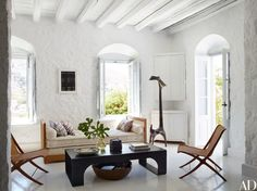Danish wicker chairs and a 1950s caned daybed surround an iron cocktail table in the living room of designer Tino Zervudachi's home on the Greek island of Hydra.