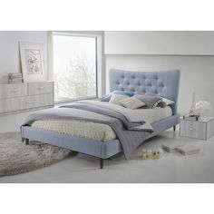 Elegantly and sculpturally designed, the Hermia Mid-century Modern Sky Blue Fabric Platform Bed features graceful curves with button-tufting detailing.